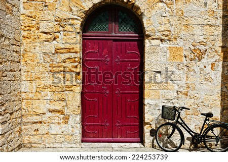 Bike near the Solid Wooden Door in the French City - stock photo