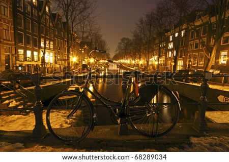 Bike on a medieval bridge in Amsterdam the Netherlands at night - stock photo