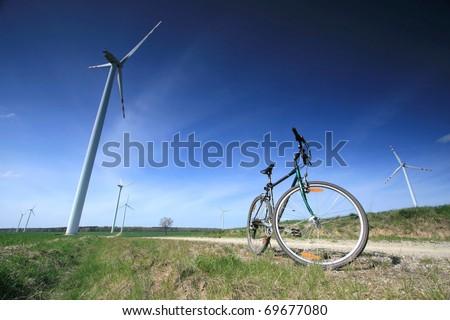 Bike on the windmill farm. - stock photo