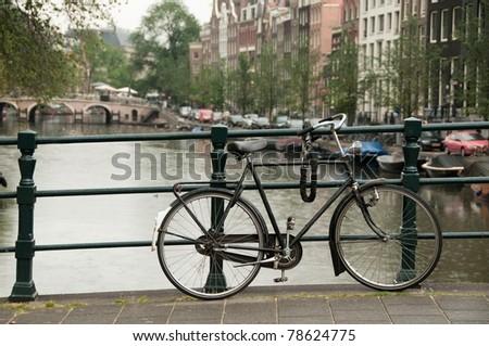 Bike parked on Lijnbaansbrug bridge on Amsterdam canal, Netherlands - stock photo