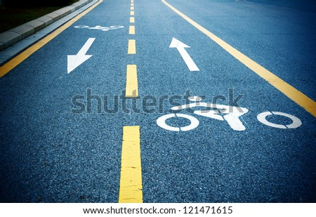 Bike path, dark road and yellow lines. - stock photo