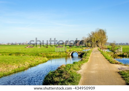 Bike path through a typical Dutch rural landscape with small streams,  meadows with grazing animals and in the background two windmills. It's a sunny day in the fall season. - stock photo