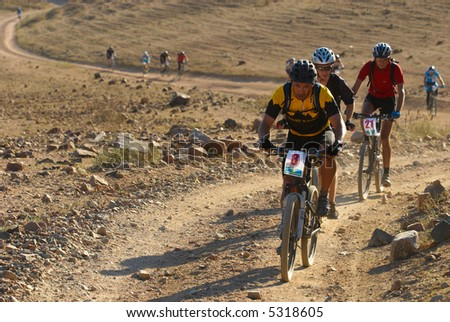 Bike race in desert mountains - stock photo