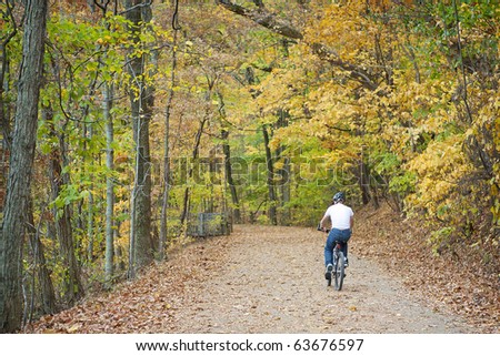 bike rider on trail in autumn woods - stock photo