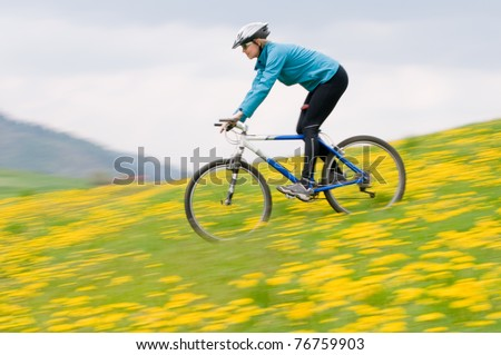 Bike riding - woman downhill on bike in dandelion  (intentional motion blur) - stock photo
