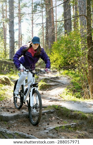 Bike riding - woman on bike in forest - stock photo