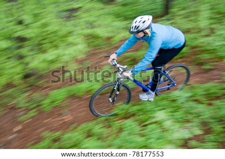 Bike riding - woman on bike (intentional motion blur) - stock photo