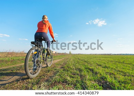 Bike riding - Young woman trying to ride on a bicycle in nature offroad - stock photo