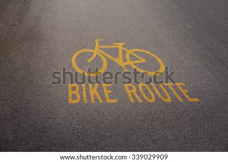 Bike route yellow sign show direction on surface of street, for Business concept or background and texture - stock photo