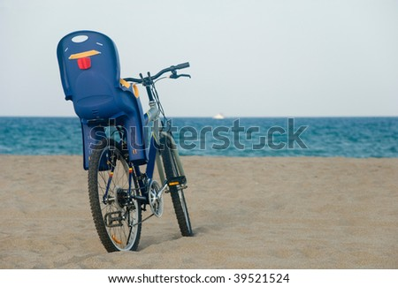 Bike with baby seat on the sand at the beach