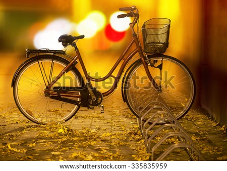 Bike with basket in bicycle rack on autumn evening, with city lights in background and leaves on ground. - stock photo