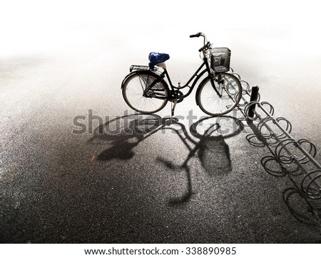 Bike with basket parked in bicycle rack with bright background and shadow on asphalt on autumn evening
