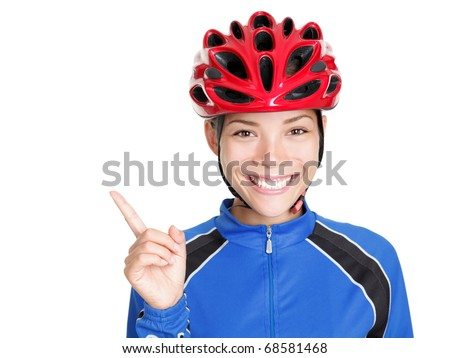 Bike woman wearing bicycle helmet pointing at copy space isolated on white background. Beautiful young asian chinese / white caucasian woman in biking outfit and red biking helmet - stock photo