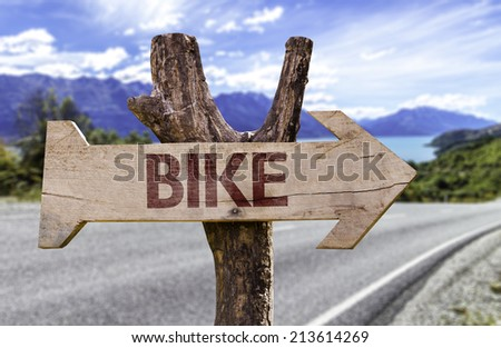Bike wooden sign with a street background  - stock photo
