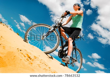 bikecyclist  in the desert against blue sky - stock photo