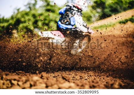 Biker accelerating during a motocross race with lots of mud and debris - stock photo