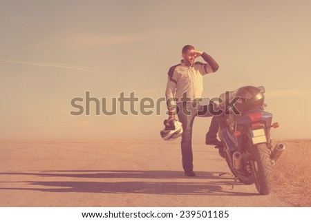 Biker chasing the sun. - stock photo