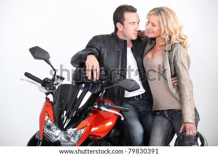 Biker couple gazing into each other's eyes. - stock photo