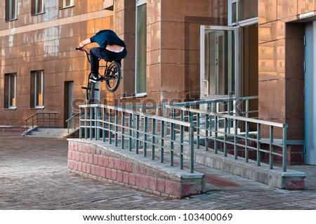 Biker doing high rail hop trick on bmx, back view - stock photo