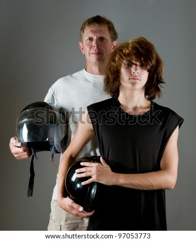 Biker family: father and son (with long punk hair) holding motorcycle helmets - stock photo