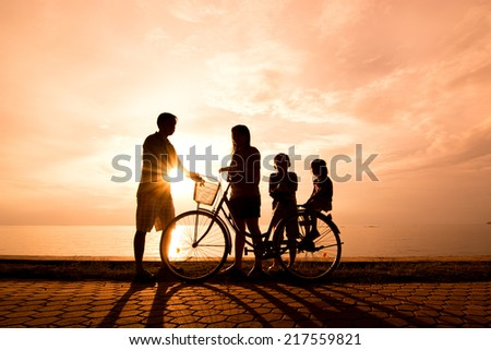 Biker family silhouette , family at the beach at sunset. - stock photo