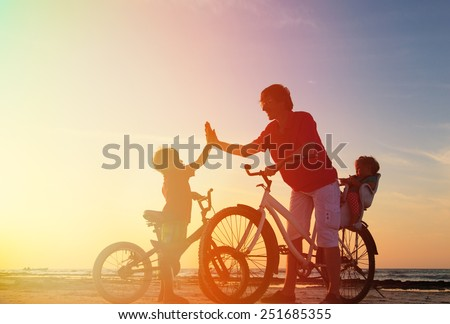 Biker family silhouette, father with two kids on bikes - stock photo