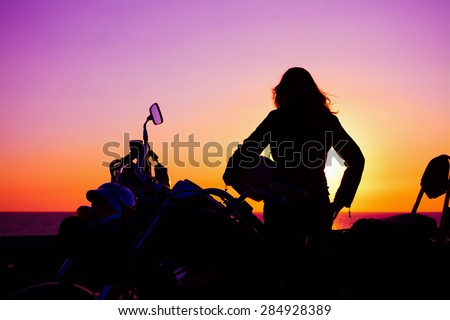 biker girl and classic motorcycle at sunset - stock photo
