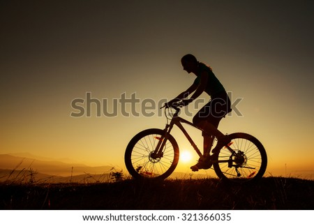 Biker-girl at the sunset on mountains - stock photo