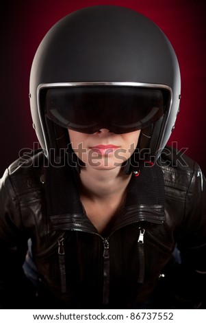 Biker girl in a helmet on a red background