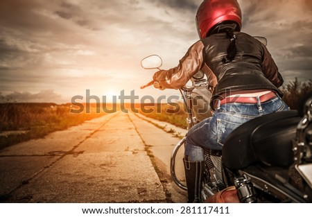 Biker girl in a leather jacket and helmet on a motorcycle. Focus on the fuel tank - stock photo