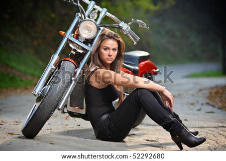 Biker girl sitting next to a bike - stock photo