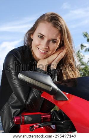 Biker girl sitting on her bike on blue sky background - stock photo