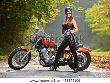 Biker girl standing next to a motorcycle - stock photo