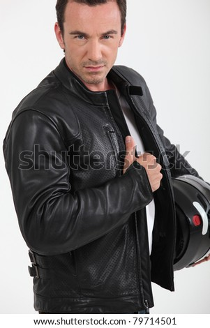 Biker holding jacket - stock photo