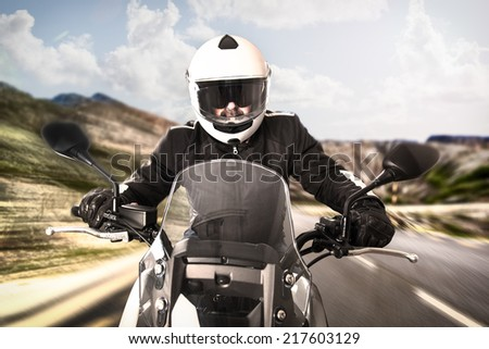 Biker in helmet and black jacket riding on the road. - stock photo