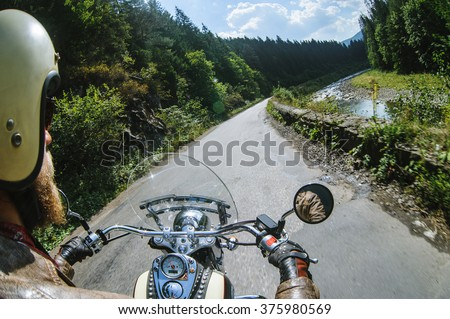 Biker in helmet driving his motorcycle on the open road by the river. First-person point of view. Focus is on the dashboard and hands - stock photo