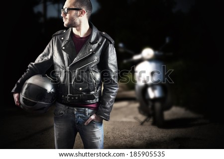 Biker in leather jacket and sunglasses posing with his scooter in an empty street - stock photo