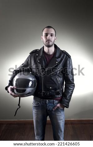 Biker in leather jacket posing holding his helmet - stock photo