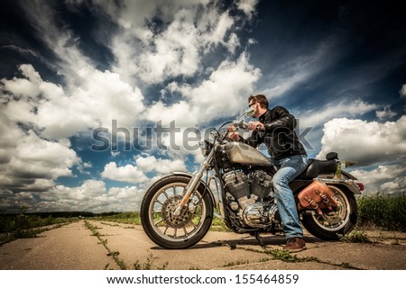 Biker in sunglasses and leather jacket on the road - stock photo