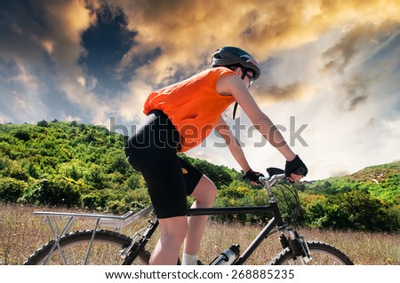 Biker in the mountains at sunset - stock photo