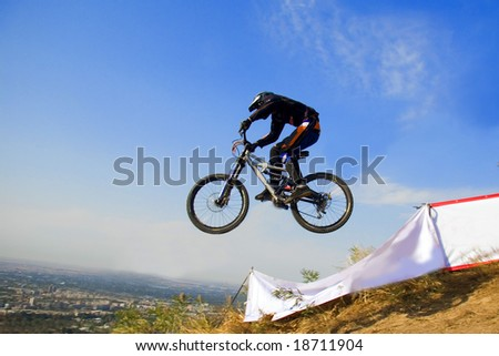 Biker jump in mountains,  Competition - stock photo