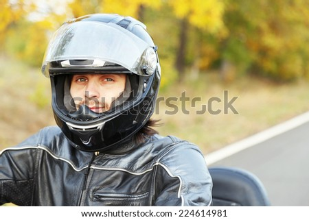Biker man in black helmet sits on bike - stock photo