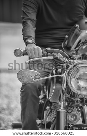 Biker man sitting on his motorcycle, black and white style - stock photo