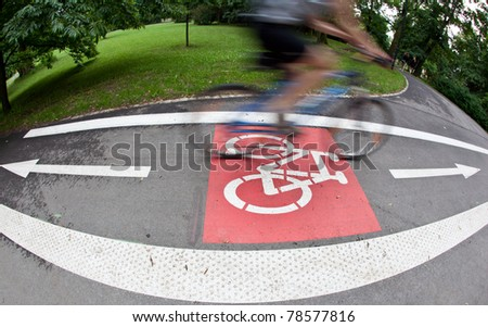 biker on a biking path in a city park (motion blur is used to convey movement) - stock photo