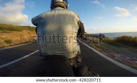 biker on a classic motorcycle seen from behind