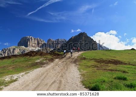 biker on high mountain road, Italian Dolomites - stock photo
