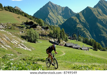 Biker on high mountain rural road; alpine scenic, Italy, Europe. - stock photo