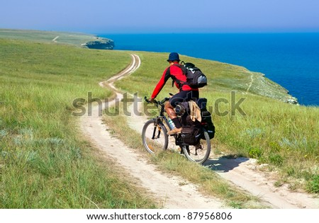 biker on meadow near sea