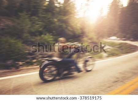 biker on mountain highway, riding around a curve with a motion blur toned with a retro vintage instagram filter app or action - stock photo
