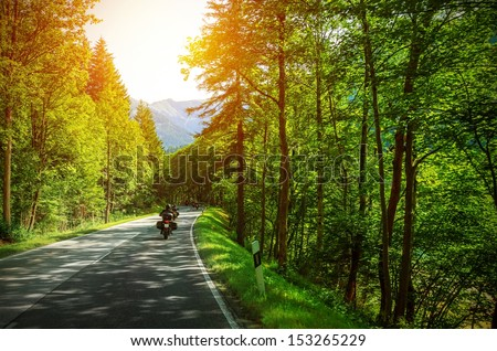 Biker on mountainous road in sunset light, motorcyclist on highway, drive motorbike along Alps, Europe trip, beautiful forest, active lifestyle - stock photo